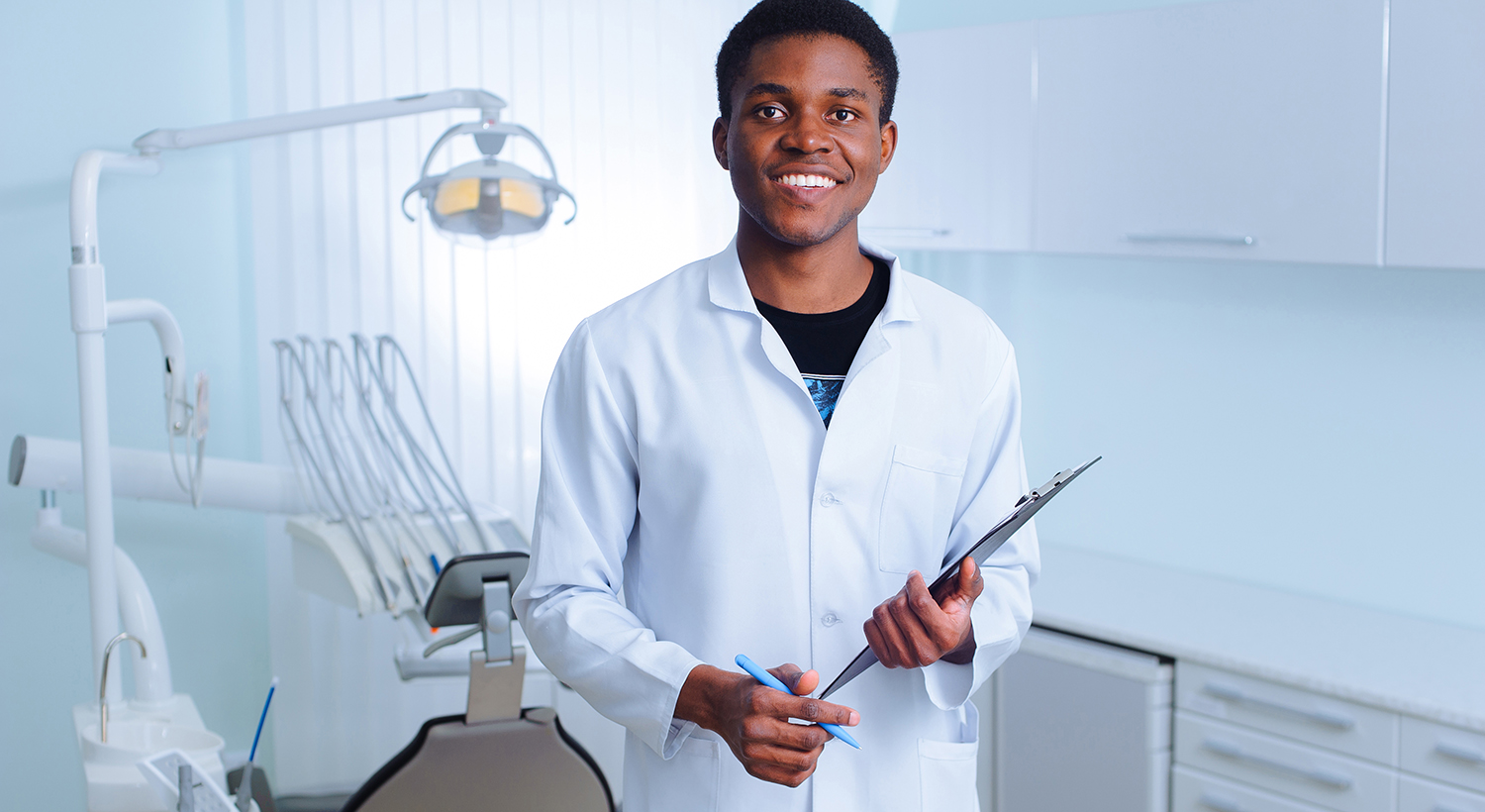 African dentist smiling - healthcare in the gambia