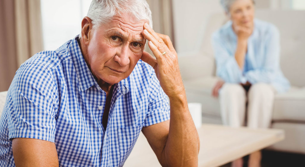 Worried Senior Man Sitting On Sofa In Living Room