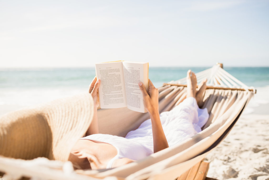 Woman reading a book on the side of the beach